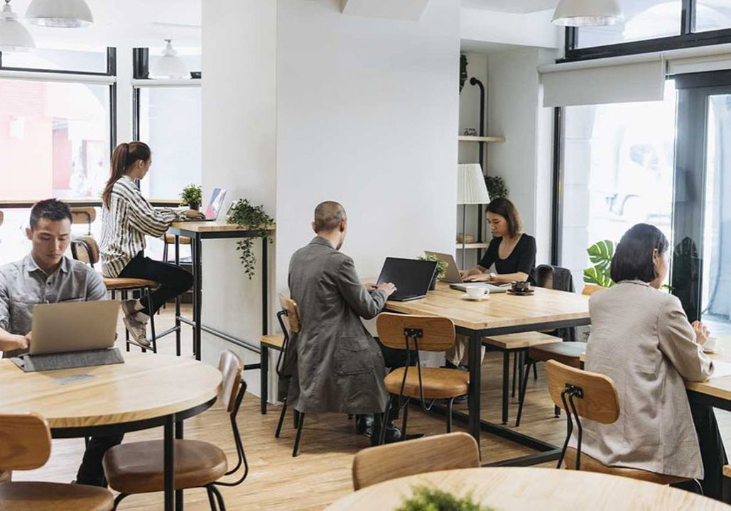 Coworkers sitting at tables independently and using laptops, digital nomad, hot desking, freelancing